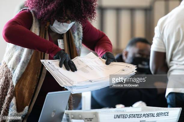 Fulton county worker moves a stack of absentee ballots at State Farm Arena on November 6 2020 in Atlanta Georgia The 2020 presidential race between...