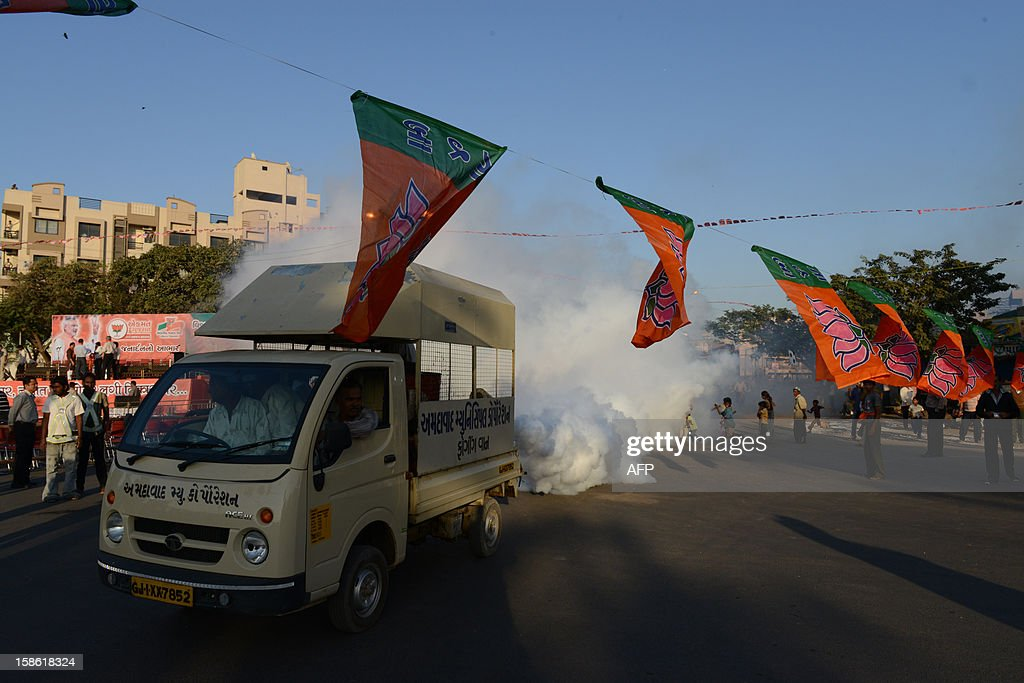 A fumigation vehicle from The Ahmedabad Municipal Corporation passes under a line of Bharatiya Janta Party (BJP) flags at the venue addressed by Chief Minister of the western Indian state of Gujarat Narendra Modi in Ahmedabad on December 21, 2012, after his victory in state assembly elections. Indian Hindu nationalist Narendra Modi should be in a strong position to run for prime minister in 2014 after winning state polls but his own party may act to stop him, newspapers said. Modi, a hardline leader of the right-wing Bharatiya Janata Party (BJP), recorded a thumping victory in his home state of Gujarat to remain as chief minister, triggering renewed speculation about his national ambitions. AFP PHOTO/Sam PANTHAKY