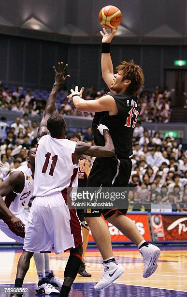 Fumihiko Aono of Japan shoots against Erfan Aseed of Qatar during the 2007 FIBA Asia Championship game at Asty Tokushima on August 05 2007 in...