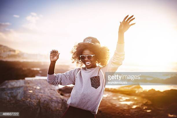 Fun African American girl laughing and dancing at the beach