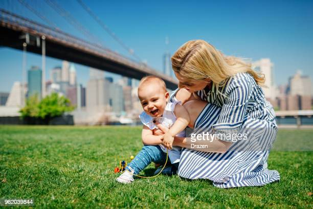 Fun and giggles in the park with mother and baby