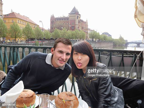 Fun couple having lunch with girl sticking tongue