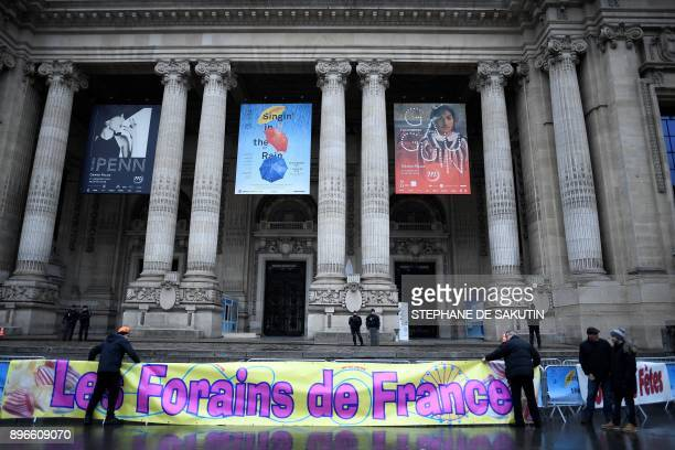 Fun fair workers set banners reading 'Fun fair workers of France' during a protest against the cancellation of 'Jours de fetes' funfair outside the...