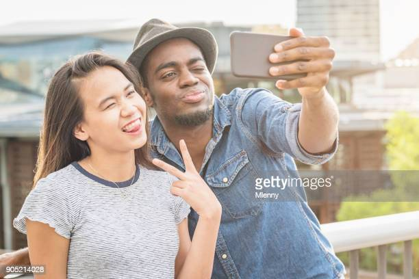 fun humor joking and grimacing young couple taking selfies with phone sydney - couple tongue kissing stock photos and pictures