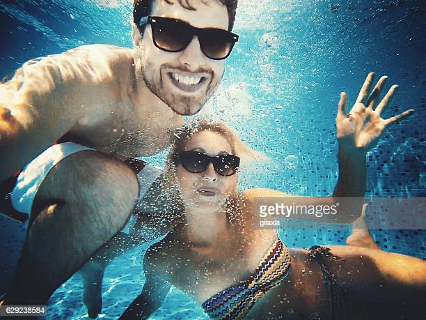 fun in a swimming pool. - heterosexual couple imagens e fotografias de stock