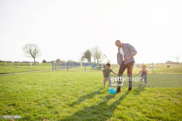 fun in the park with dad - football stock pictures, royalty-free photos & images