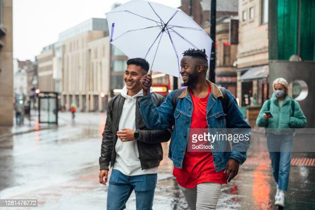 fun in the rain - high street stock pictures, royalty-free photos & images