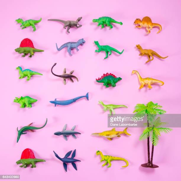 Fun Knolling Layout of Plastic Dinosaurs On Bright Paper