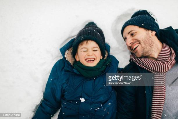 fun on the snow - snow angel stock photos and pictures
