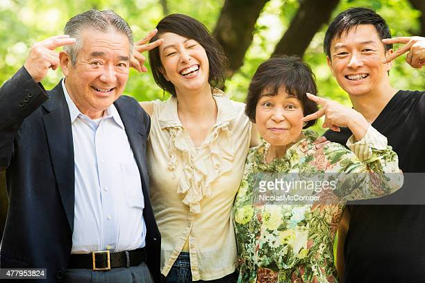 Fun peace signs mature Japanese family portrait in Yoyogi park