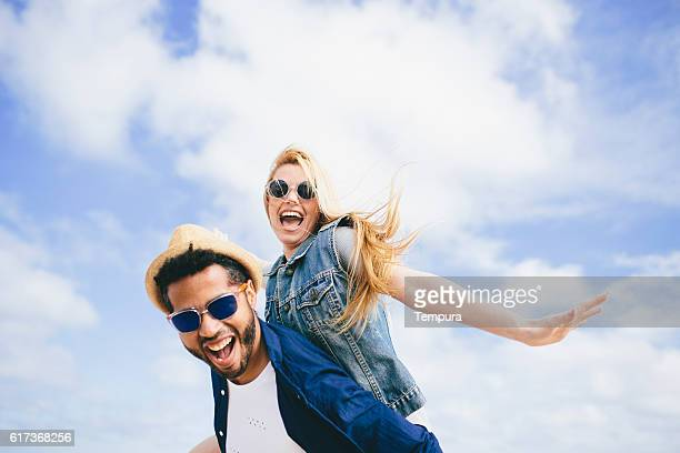 Fun piggyback against a cloudy blue sky