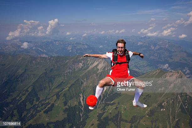Fun skydiver is playing a soccer game in the sky.