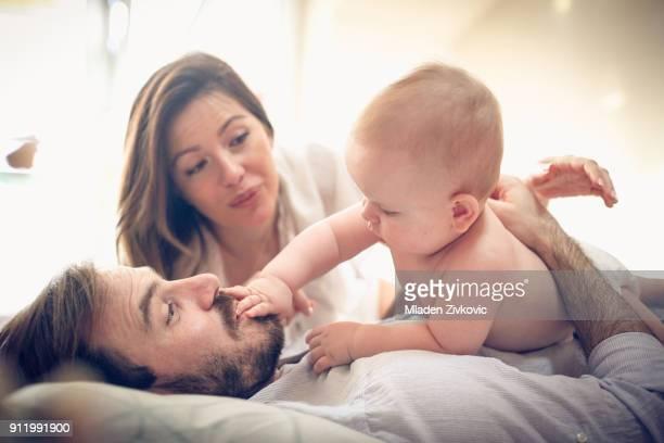 diversión con el niño. - pareja abrazados cama fotografías e imágenes de stock