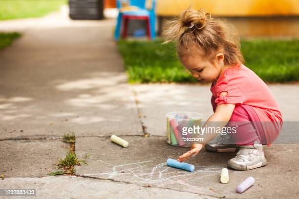 fun with chalks for a girl in her back yard - toddler stock pictures, royalty-free photos & images