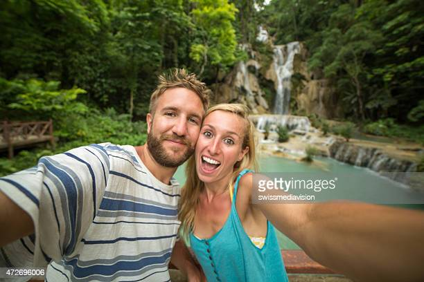 Fun young couple taking selfie at waterfalls