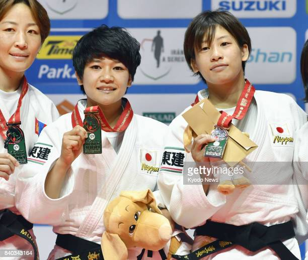 Funa Tonaki of Japan poses for photos after winning the women's 48kilogram final at the world judo championships in Budapest on Aug 28 2017 Alongside...