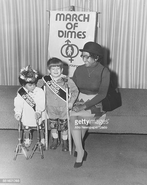A fund raising event an AfricanAmerican woman on a stage with two children wearing callipers on their legs holding crutches at a fundraiser for...