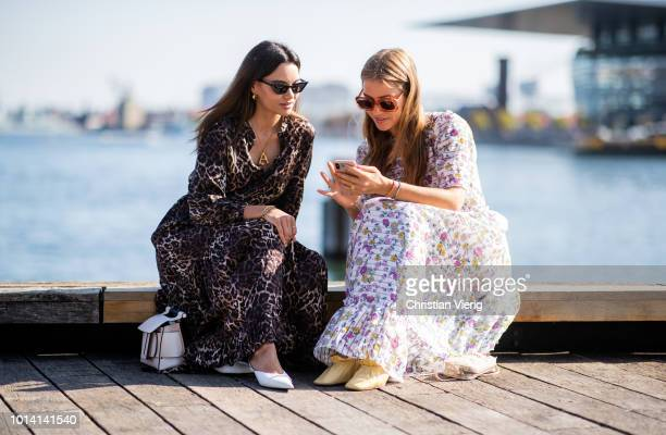 Funda Christophersen wearing dress with animal print and Trine Kjaer wearing dress with floral print seen outside Munthe during the Copenhagen...