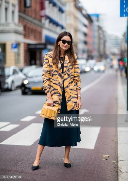 Funda Christophersen wearing yellow bag dress coat with animal print tiger seen outside Moire during Oslo Runway SS19 on August 15 2018 in Oslo Norway