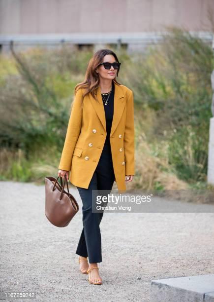 Funda Christophersen wearing yellow blazer brown triangle bag outside Samsøe Samsøe during Copenhagen Fashion Week Spring/Summer 2020 on August 07...