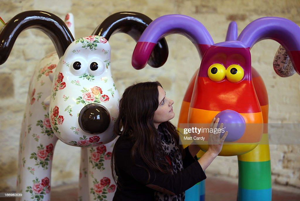 Fundraising manager Lauren Vincent poses with two Gromit sculptures, out of around 70 which have been painted by celebrity artists, (L-R) Cath Kidston and Richard Williams before they are placed around the London for public view as part of charity initiative arts trail, on April 19, 2013 in Bristol, England. After being displayed to the public from July 1, the sculptures will be eventually auctioned off to raise funds for the Bristol Children's Hospital charity, Wallace & Gromit's Grand Appeal.