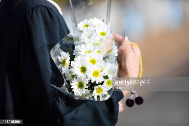a funeral and visit to a grave of japan. the woman of the senior worships the ancestral soul in a black mourning dress. i hold white chrysanthemum bunch and beads in a hand. - funeral imagens e fotografias de stock