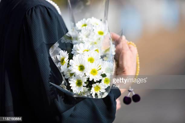 een begrafenis en bezoek aan een graf van japan. de vrouw van de senior verering van de voorouderlijke ziel in een zwarte rouw jurk. ik houd witte chrysant stelletje en kralen in een hand. - begrafenis stockfoto's en -beelden