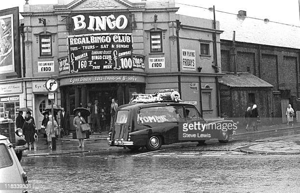 A funeral cortege passes the Regal Bingo Club on the corner of Chant Street in the east London borough of Newham circa 1965