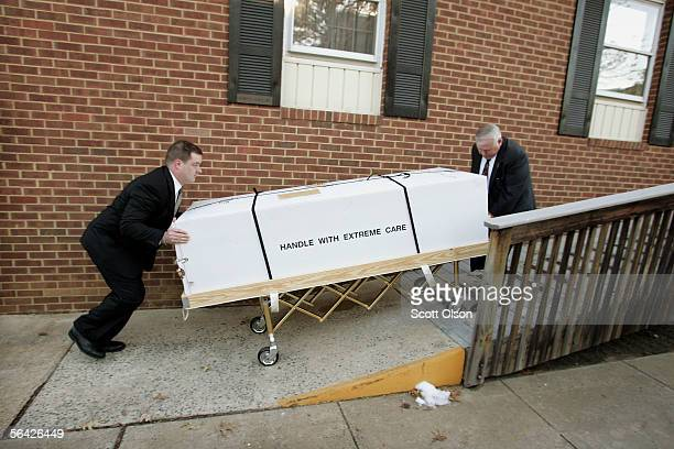 Funeral director apprentice Chris Moore and funeral director Bob Petty wheel the remains of Marine LCpl Andrew Patten into Murphy Funeral Home...