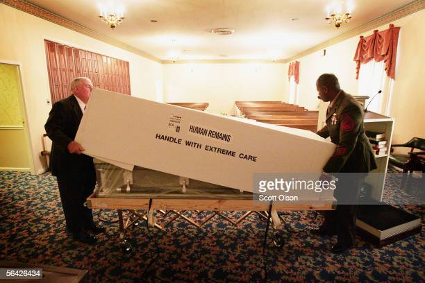 Funeral director Bob Petty and US Marine SSgt Eugene Bristol unpack the remains of Marine LCpl Andrew Patten at Murphy Funeral Home December 13 2005...