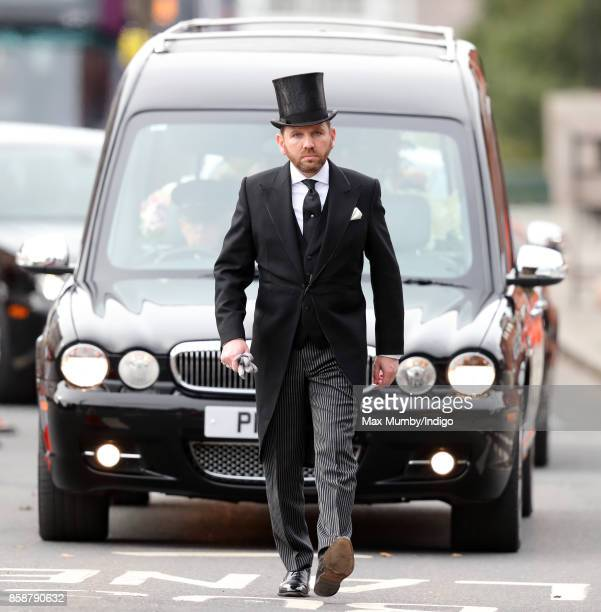 A funeral director leads a hearse carrying Liz Dawn's coffin to Salford Cathedral for her funeral service on October 6 2017 in Salford England...