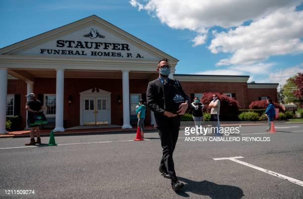 Funeral Director Sean Johnson carries ashes to a family waiting in the parking lot as other people wait in line outside the Stauffer Funeral Homes to...