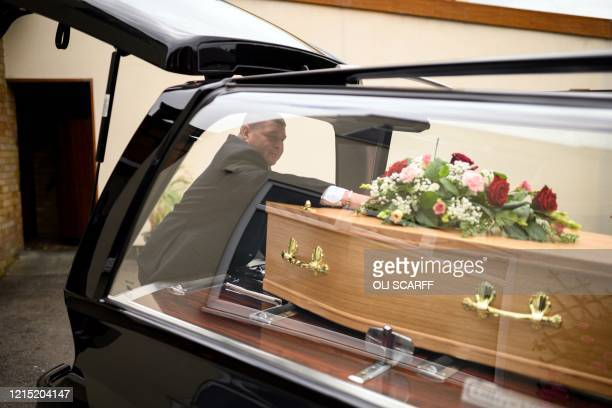 Funeral director Wesley Weibrecht places a floral tribute on the coffin of a person who had tested positive for Covid-19 prior to departing the...