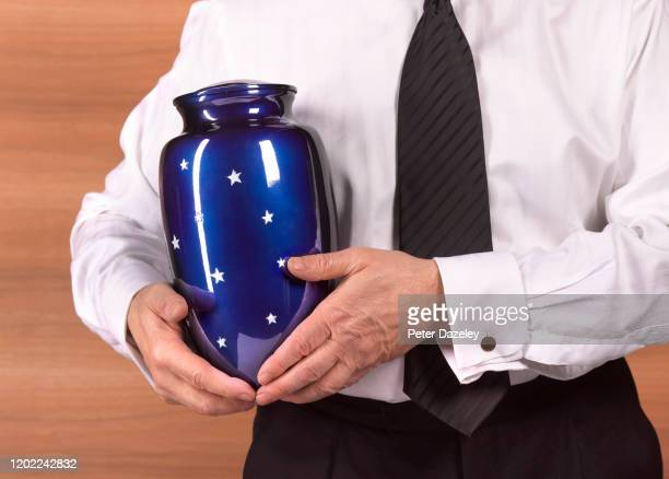 funeral director with cremation urn - urn stock pictures, royalty-free photos & images