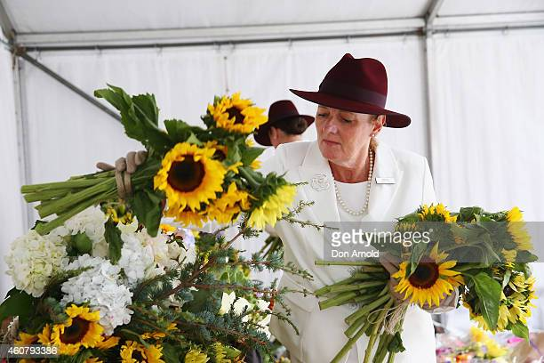 Funeral directors lay flowers at a wreath laying ceremony after the funeral for Tori Johnson at Martin Place on December 23 2014 in Sydney Australia...