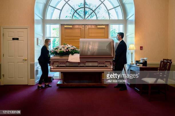 Funeral Home Director Chris Fontana and apprentice Christina Smith position Mrs. Barbara Lipscomb's coffin in front of the door, as they prepare a...