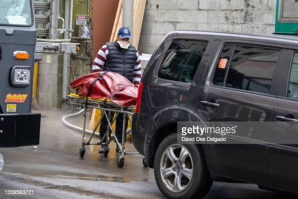 Funeral home employee loads a body to be transported a refrigerated trailer on April 9, 2020 in New York City. New York Governor Andrew Cuomo said...