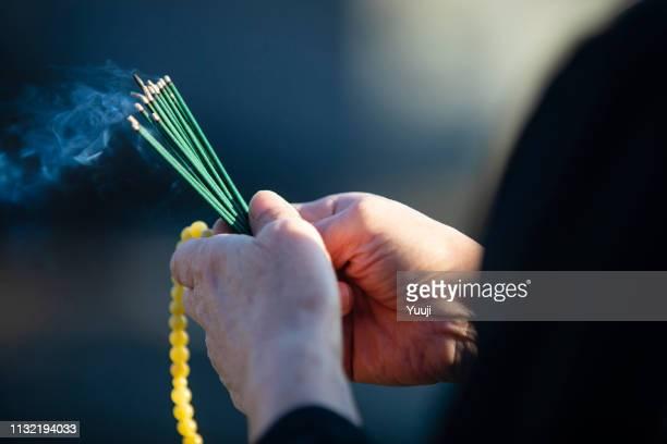 日本での葬儀と墓への訪問.シニアの女性は、黒い喪服を着てビーズやお香のスティックを持っています。香の杖から煙が出てくる。 - 葬儀 ストックフォトと画像
