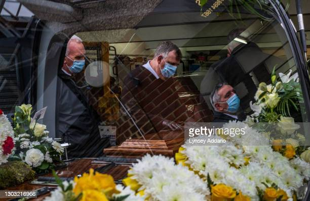 Funeral Operative Steve Carter shines the nameplate on his friend's coffin--a victim of COVID-19--before bringing the coffin to the crematorium from...