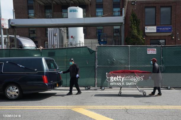 Funeral parlor workers move a body from a refrigeration truck serving as a temporary morgue at the Brooklyn Hospital Center to a hearse in the...
