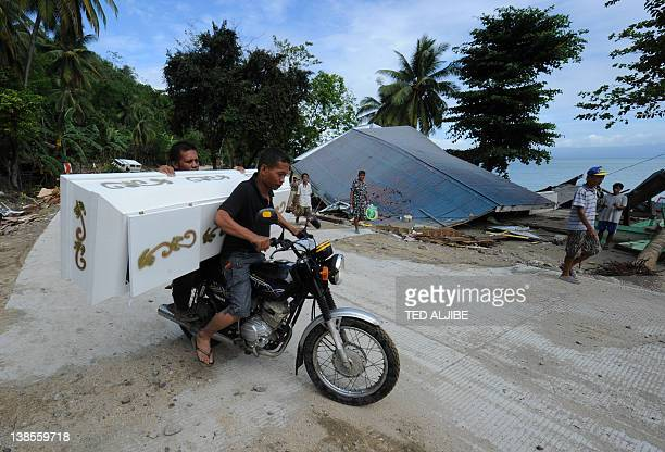 Funeral parlor workers transport past damaged houses destroyed at the height of the powerful earthquake in La Libertad town, Negros Oriental...