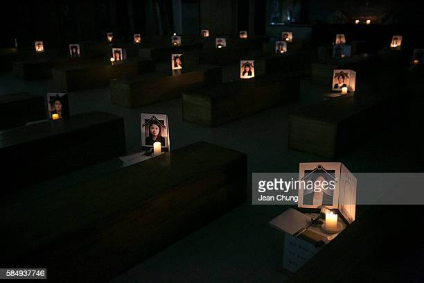 Funeral photos of the participants of Death Experience/Fake Funeral are illuminated by candle lights on the coffins on August 1 2016 in Andong South...