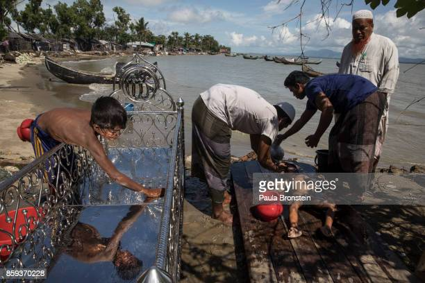 Funeral procedures take place for five children after an overcrowded boat carrying Rohingya fleeing Myanmar capsized overnight killed around 12...