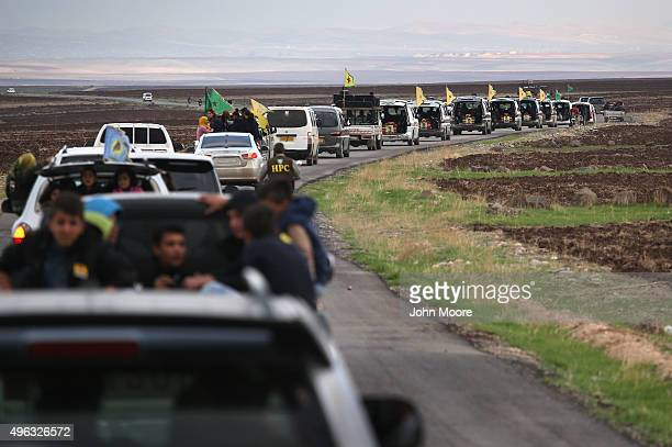 A funeral procession carries eight members of the People's Protection Units to a martyrs' cemetery on November 8 2015 in Derek Rojava Syria Seven of...