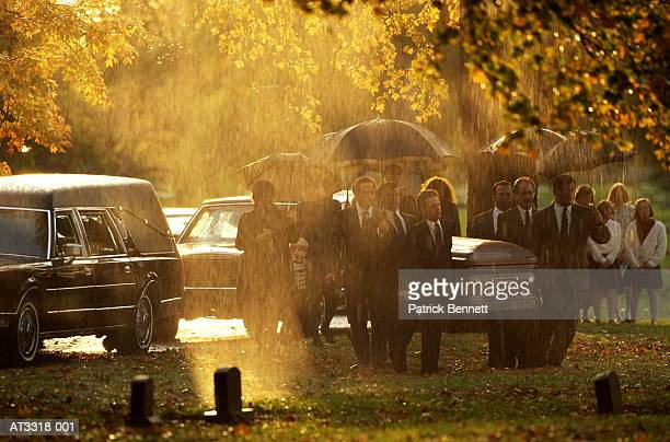 funeral procession in cemetery during rainstorm, indiana, usa - pallbearer stock photos and pictures