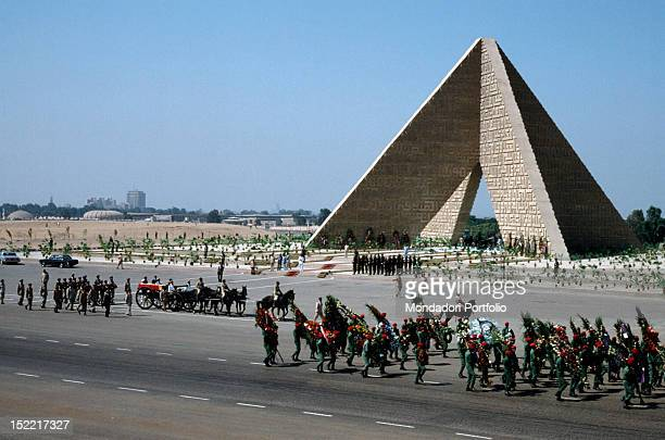 Funeral procession of Egyptian Sadat President the coffin is put down on a carriage cannon and walk in front of a Pyramid mausoleum of the unknown...