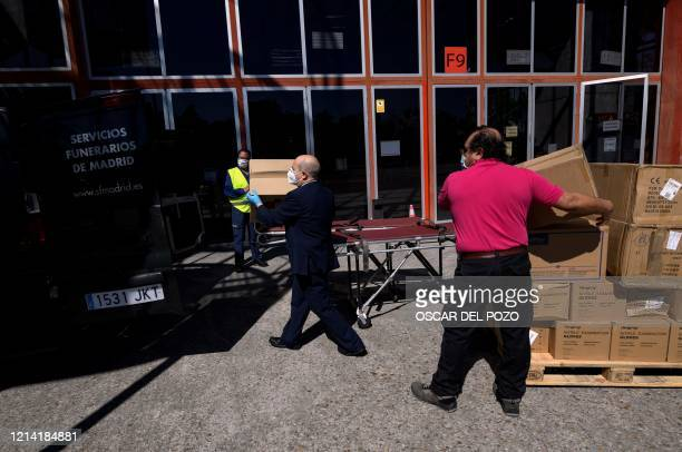 Funeral service employees unload boxes containing sanitary material donated by the city of Beijing to the City of Madrid, at the Casa de Campo's...