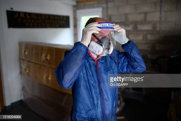 Funeral service operative Howard Jackson wears the personal protective equipment necessary for handling the body of a person who had tested positive...