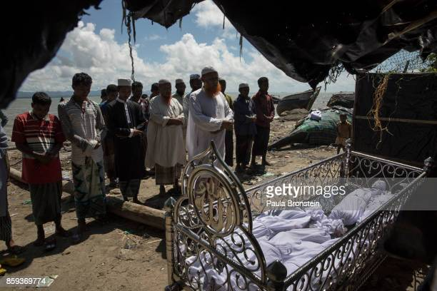 A funeral takes place for five children after an overcrowded boat carrying Rohingya fleeing Myanmar capsized overnight killed around 12 people...