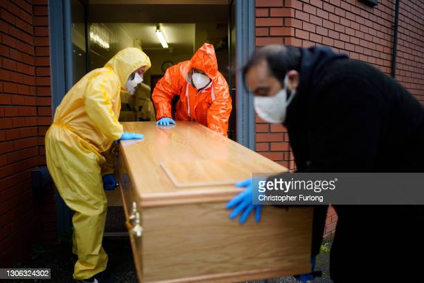 Funeral volunteers begin to transport a coffin after performing Ghusl, the sacred Islamic ritual of bathing the deceased, on a Covid-19 positive...